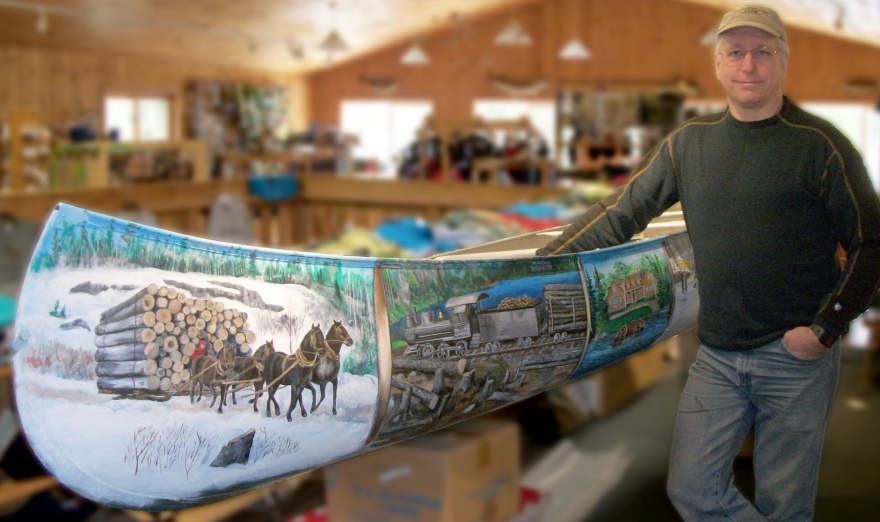 Joe Baltich, Jr. standing with his painted historical account of the BWCA region, past and present