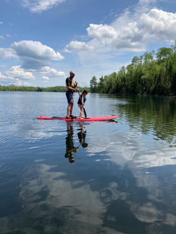 Stand up paddle boarding with Dad on Jasper Lake at Northwind Lodge
