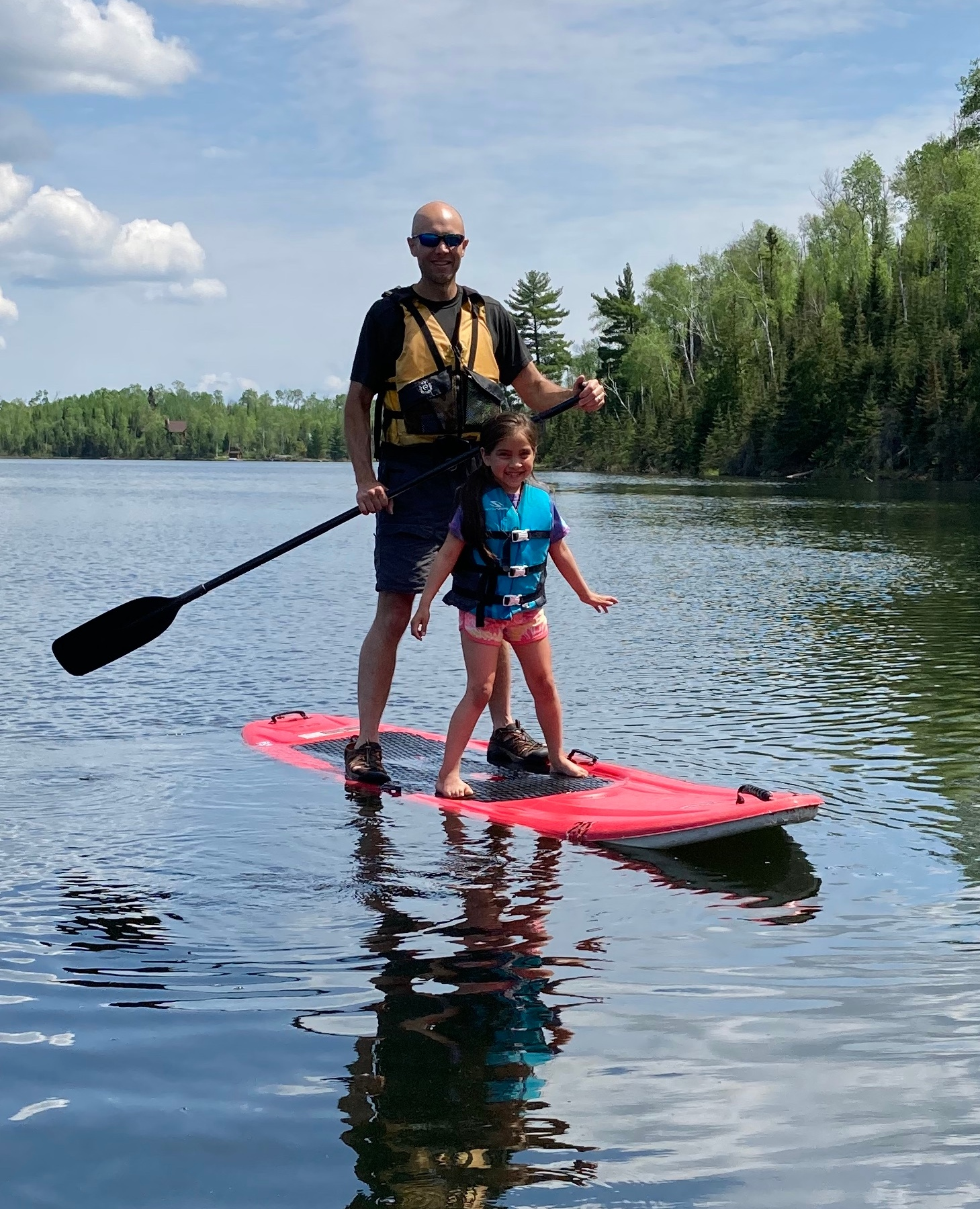 May paddle-boarding Dad on Jasper Lake at Northwind Lodge. Water is still cold!